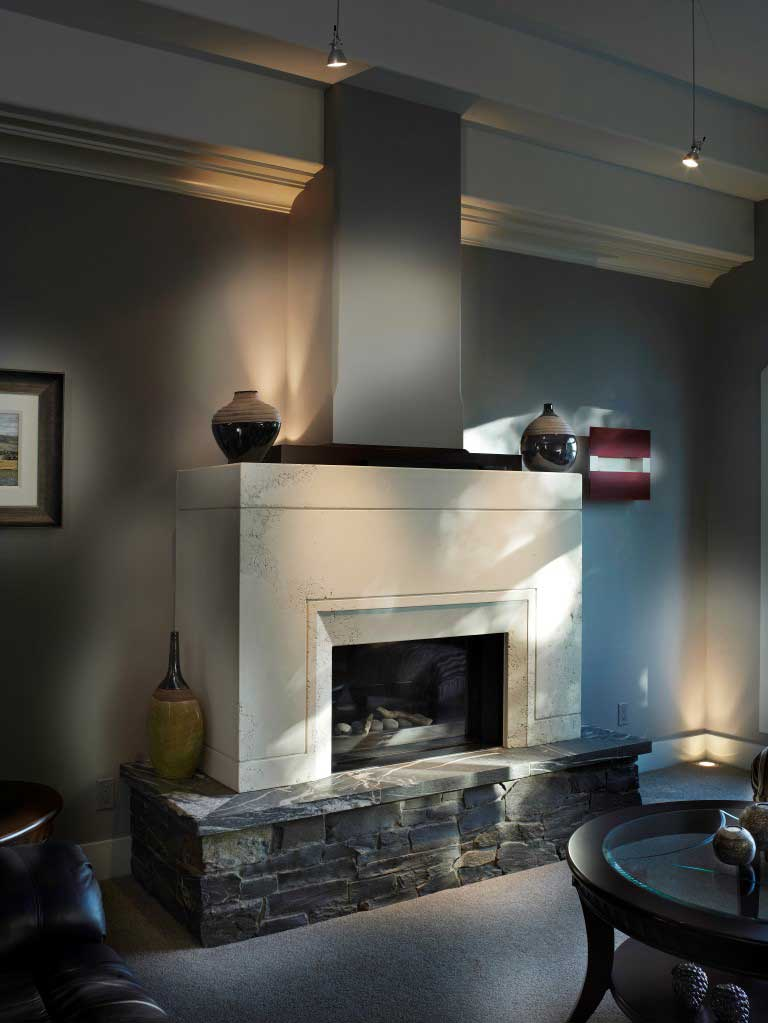 stone fireplace in a grey living room with potlights on