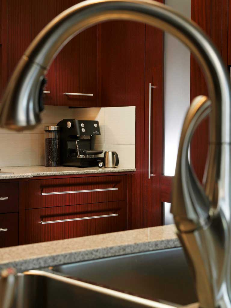 grey stainless steel faucet with custom wooden kitchen cabinetry in the background