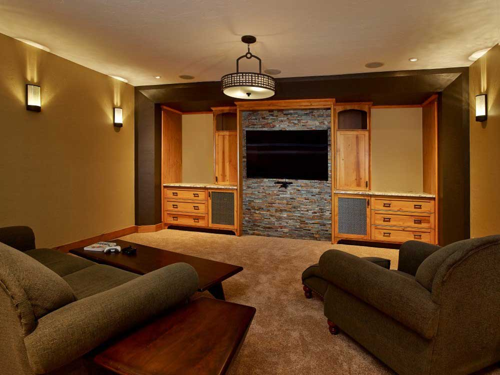 brown fabric sofa chairs in a loving room with custom wooden cabinetry surround flat screen TV