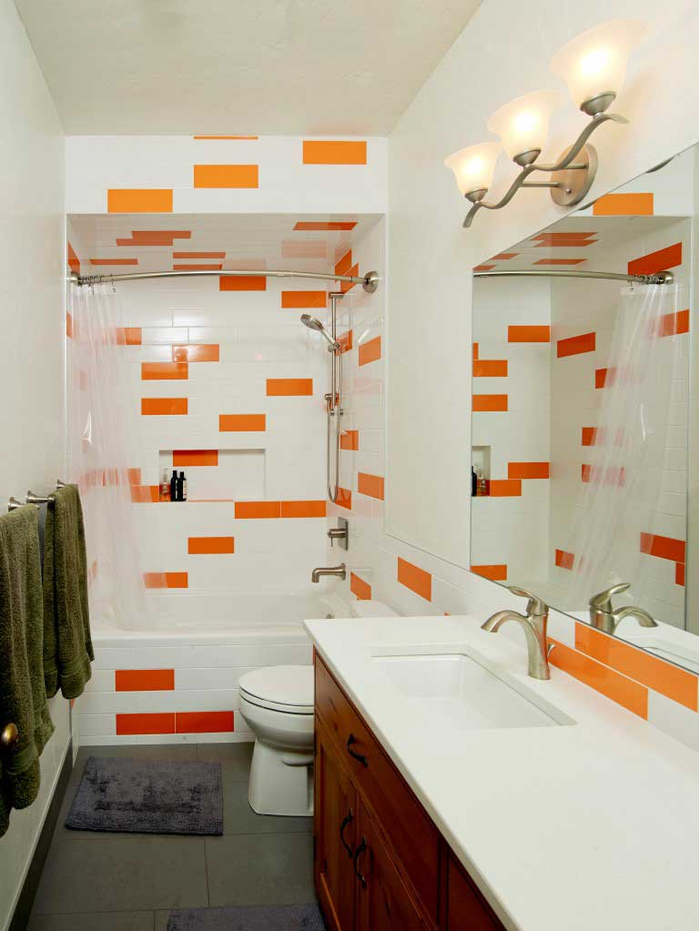 orange and white ceramic tile bathroom with custom wooden cabinets under the sink
