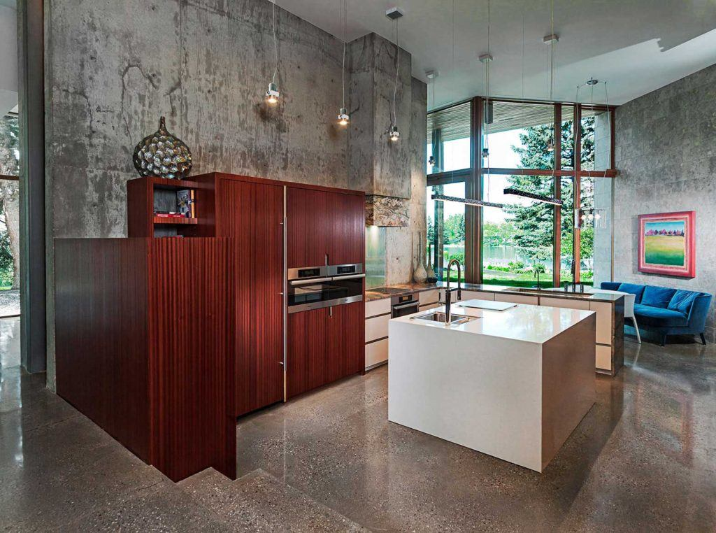 Concrete-walled kitchen with grey island and custom wooden fridge exterior