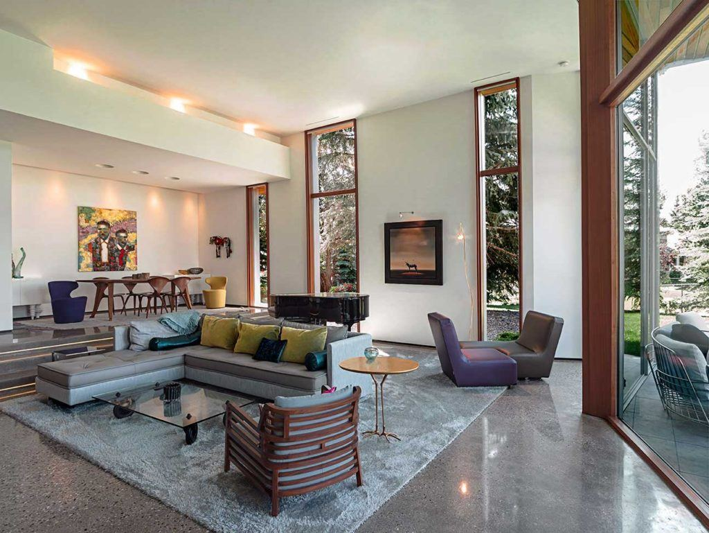Large living room space with grey sectional sofa, purple single-seat chairs, black grand piano, and custom wooden framed floor-to-ceiing windows