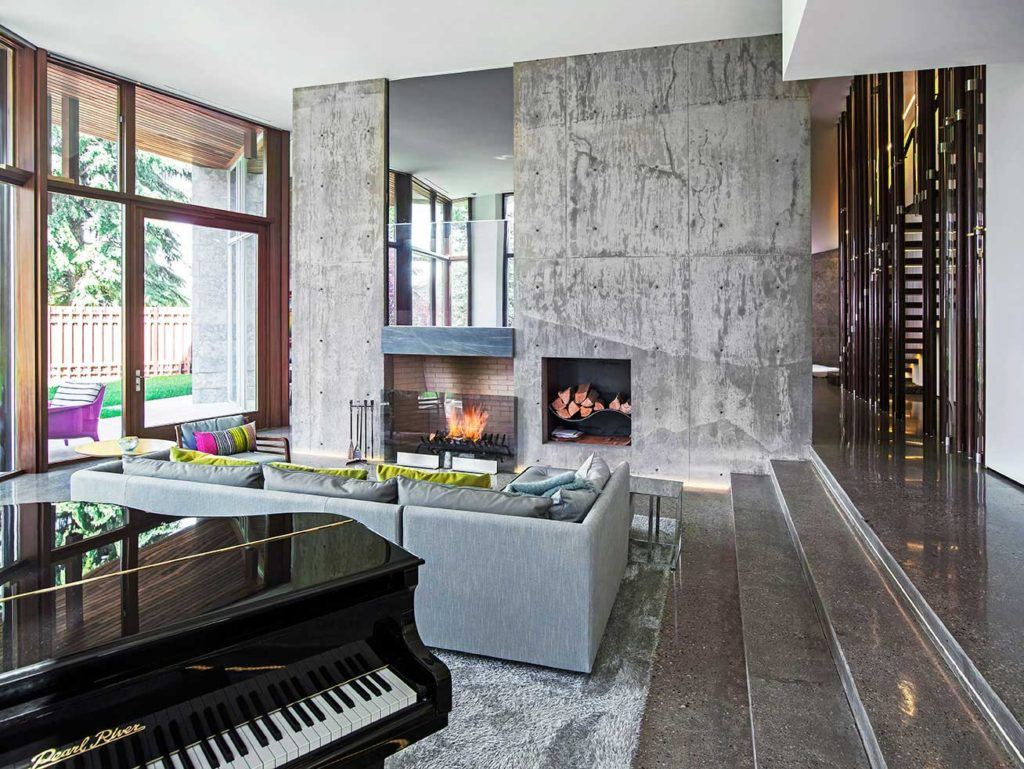 modern conrete living room with black grand piano, gray couch, fireplace, and custom woodwork windows
