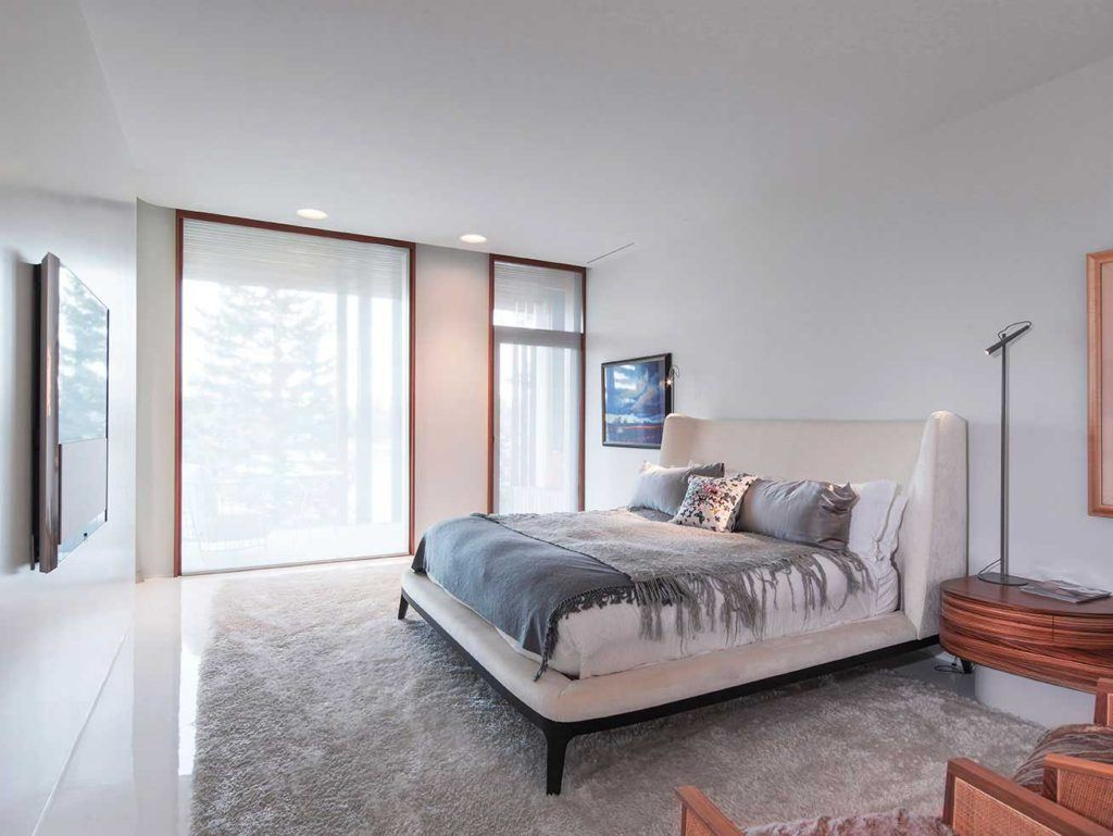 White bed with white and grey linens in white room