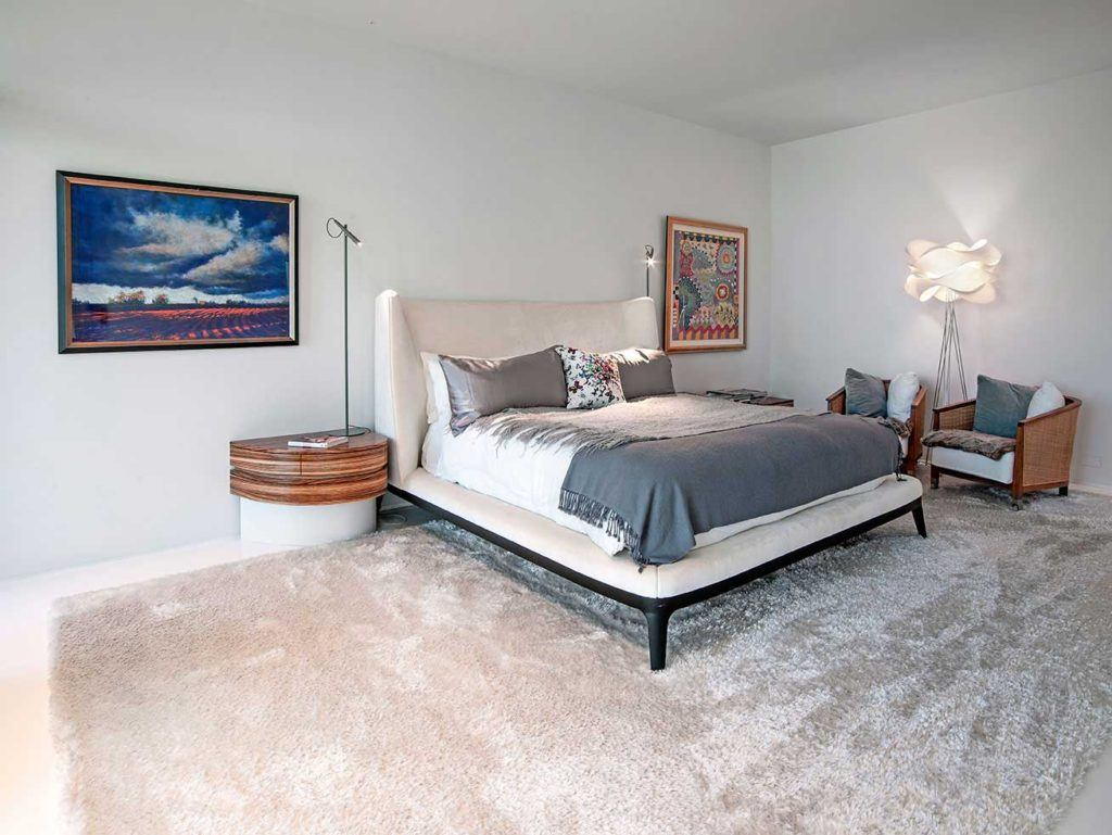 White Bed with white and gray linens in a white room with white carpet