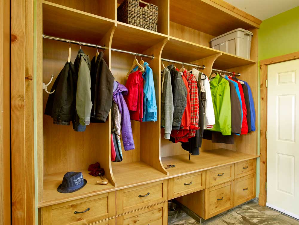 Kids' clothing hangs on custom wooden cabintry in walk-in closet