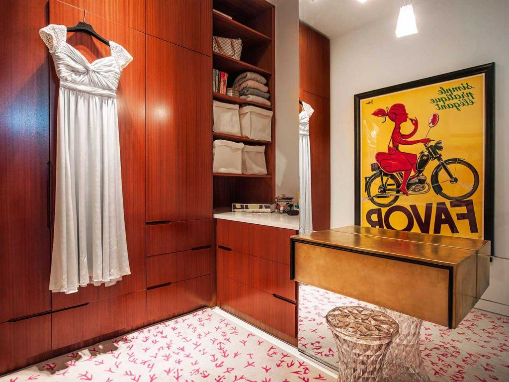 Walk-in closet with yellow artwork and a white blouse hanging from the custom wooden cabintry