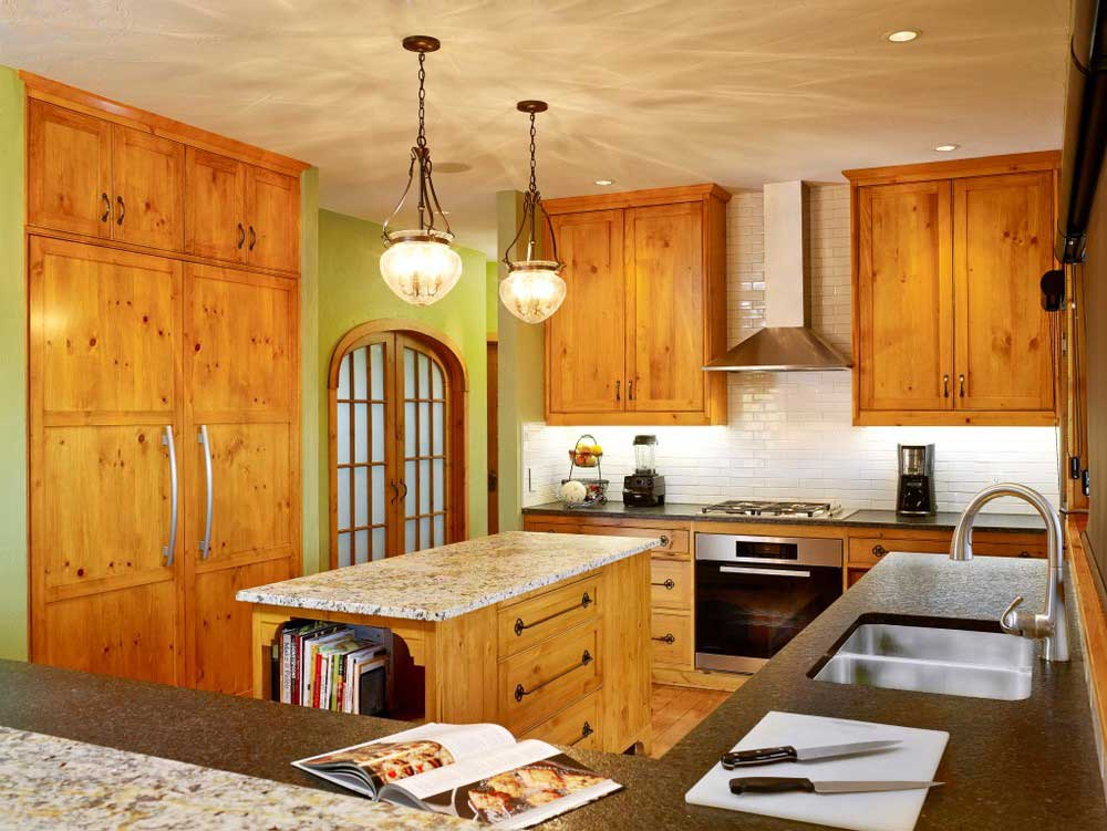 two turned-on pendant lamps above island in kitchen with custom wooden cabintry