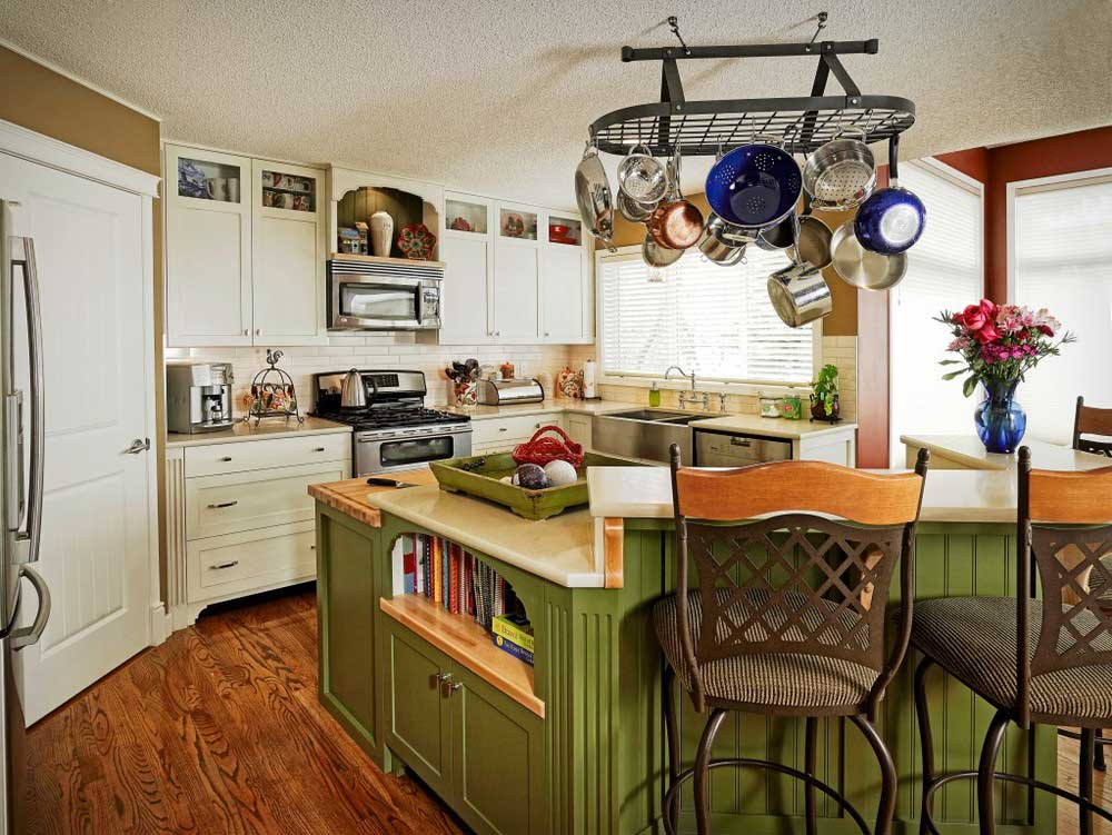 full decorated kitchen includes two bar stools, green kitchen island with white table-top, and custom white wooden cabintry