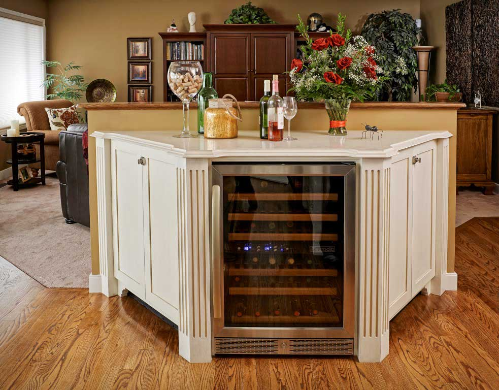 wine rack sits behind glass door in a custom white cabinet unit