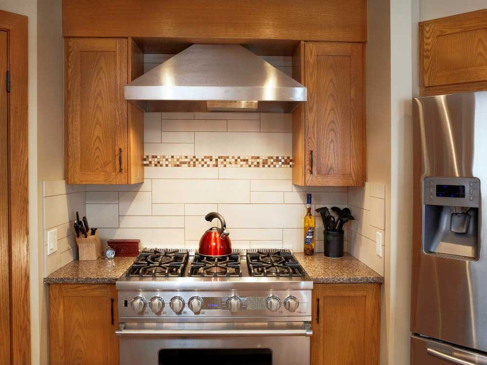 red kettle on stove range surrounding by custom wooden cabintry