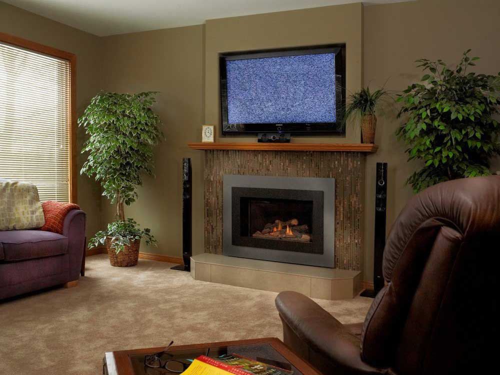 flat screen TV above electric fireplace with an empty armchair and sofa