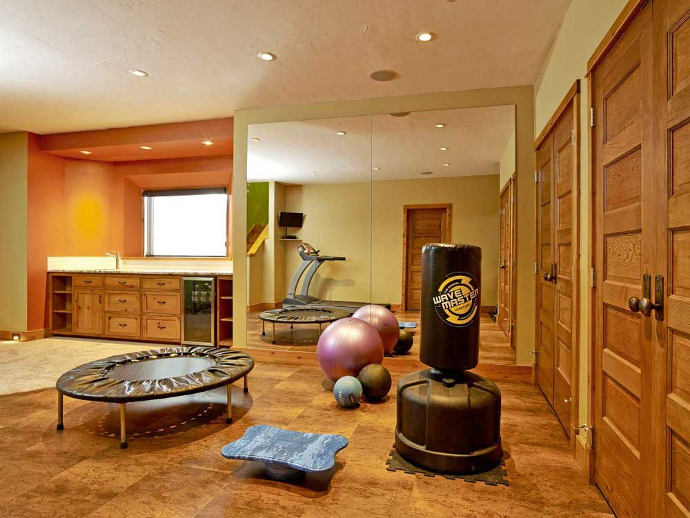 work-out room with wooden doors includes trampoline, exercise balls, and punching bag