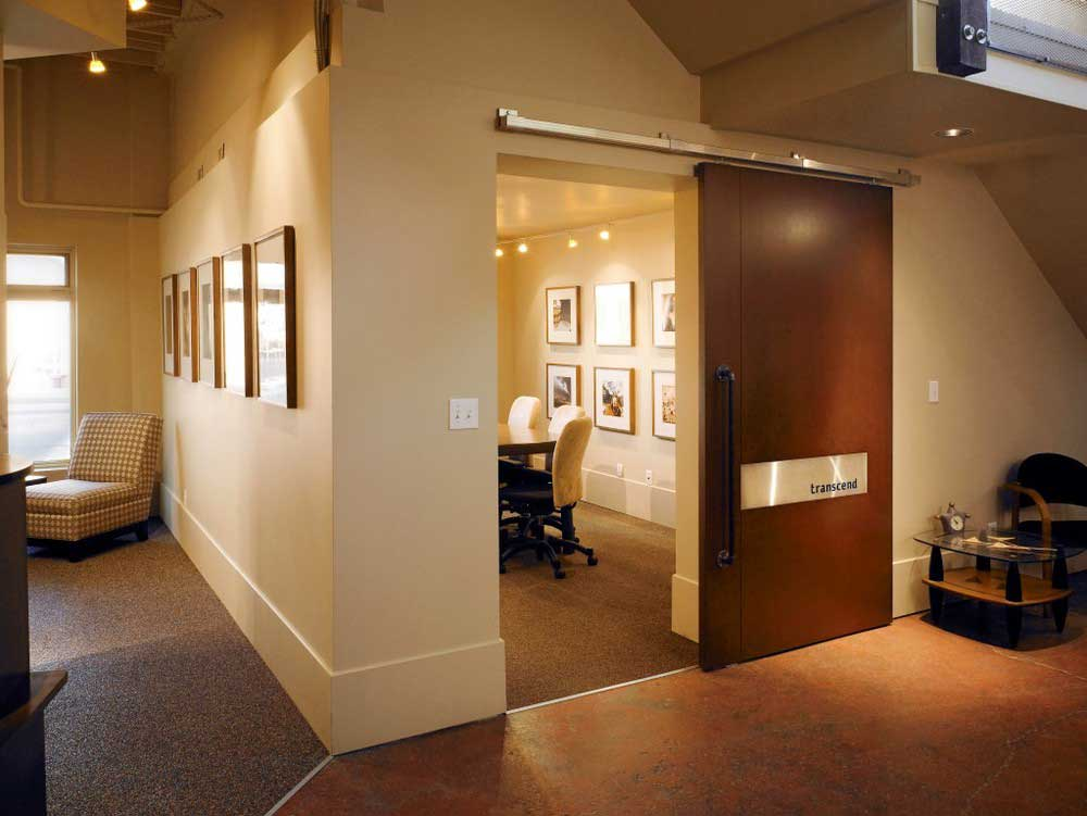 open wooden sliding door reveals conference room with table, chairs, and artwork on walls